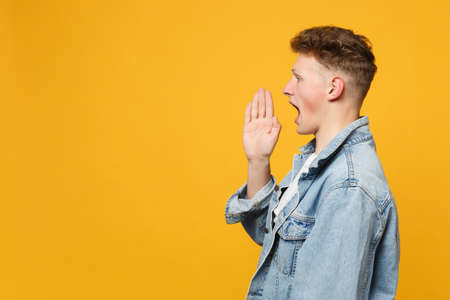 Side view of handsome young man in denim casual clothes looking aside, screaming with hand gesture isolated on yellow orange background. People sincere emotions, lifestyle concept. Mock up copy space