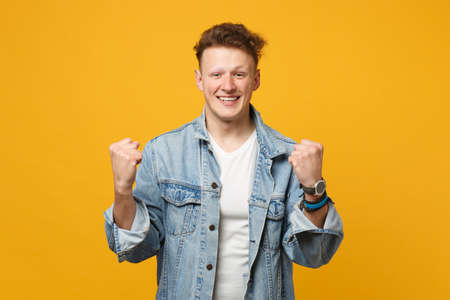 Portrait of happy young man in denim casual clothes clenching fists like winner isolated on yellow orange wall background in studio. People sincere emotions, lifestyle concept. Mock up copy space