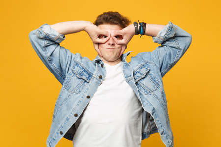 Funny young man in denim clothes blowing cheeks hold hands near eyes imitating glasses or binoculars isolated on yellow orange background. People sincere emotion lifestyle concept. Mock up copy space