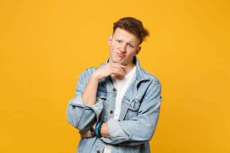 Displeased young man in denim casual clothes looking camera, put hand prop up on chin isolated on yellow orange background in studio. People sincere emotions, lifestyle concept. Mock up copy space 版權商用圖片