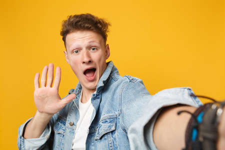 Close up selfie shot of amazed young man in denim casual clothes keeping mouth open, showing palm isolated on yellow orange background. People sincere emotions, lifestyle concept. Mock up copy space