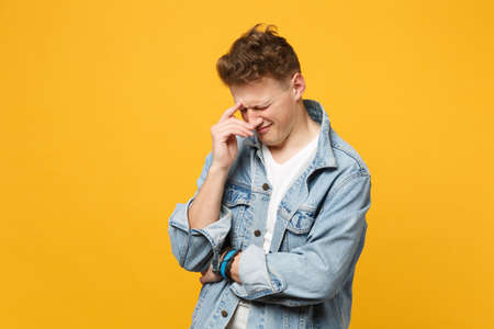 Portrait of crying dissatisfied young man in denim casual clothes with lowered head isolated on yellow orange wall background in studio. People sincere emotions, lifestyle concept. Mock up copy space Banque d'images - 124534671