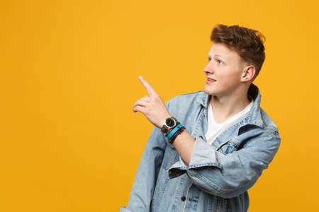 Portrait of attractive young man in denim casual clothes pointing index finger aside isolated on yellow orange wall background in studio. People sincere emotions lifestyle concept. Mock up copy space