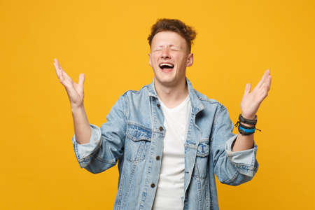 Portrait of crazy young man in denim casual clothes keeping eyes closed, spreading hands isolated on yellow orange background in studio. People sincere emotions, lifestyle concept. Mock up copy space