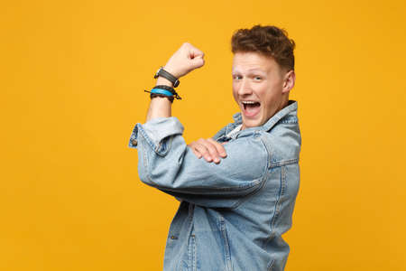 Side view of cheerful young man in denim casual clothes looking camera showing biceps, muscles isolated on yellow orange wall background. People sincere emotions lifestyle concept. Mock up copy space