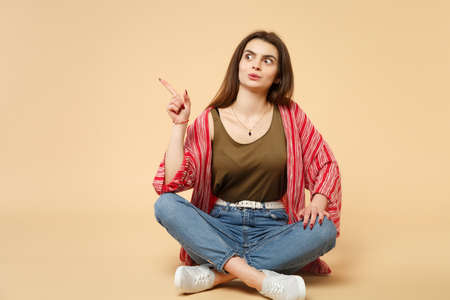 Portrait of amazed young woman in casual clothes sitting pointing index finger aside isolated on pastel beige wall background in studio. People sincere emotions, lifestyle concept. Mock up copy space