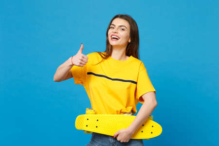 Portrait of laughing young woman in vivid casual clothes looking camera, holding yellow skateboard showing thumb up isolated on blue background in studio. People lifestyle concept. Mock up copy space