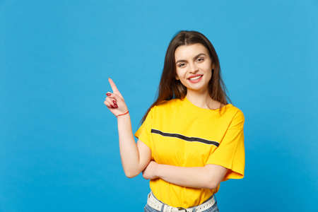 Portrait of smiling beautiful young woman in vivid casual clothes looking camera, pointing index finger aside up isolated on bright blue wall background. People lifestyle concept. Mock up copy space
