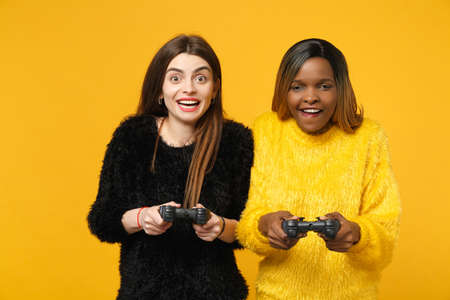 Two young women friends european and african american in black yellow clothes hold joystick isolated on bright orange wall background, studio portrait. People lifestyle concept. Mock up copy space.
