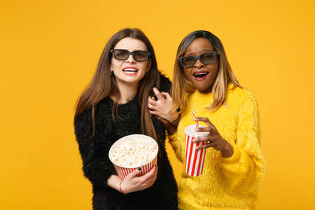 Two women friends european and african american in black yellow clothes hold bucket of popcorn isolated on bright orange wall background, studio portrait. People lifestyle concept. Mock up copy space 免版税图像