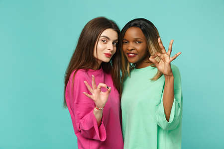 Two young women friends european and african american in pink green clothes showing OK gesture isolated on blue turquoise wall background studio portrait. People lifestyle concept. Mock up copy space