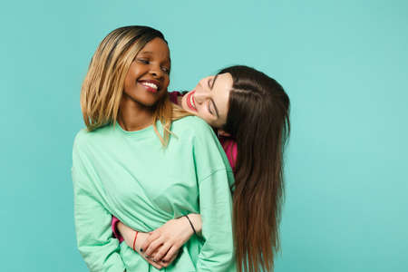 Two young women friends european and african american in pink green clothes standing posing isolated on blue turquoise wall background, studio portrait. People lifestyle concept. Mock up copy space