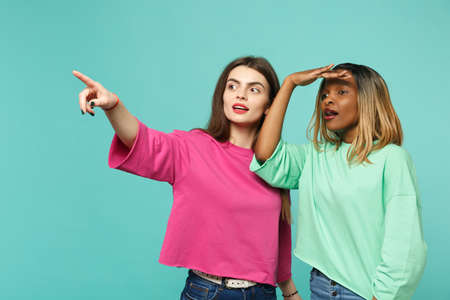 Two women friends european and african american in pink green clothes holding hand at forehead looking far away isolated on blue turquoise background. People lifestyle concept. Mock up copy space Stockfoto
