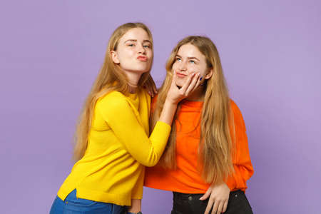 Two cheerful young blonde twins sisters girls in vivid colorful clothes having fun, fooling around isolated on pastel violet blue wall background. People family lifestyle concept. Mock up copy space