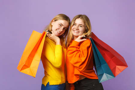 Two smiling young blonde twins sisters girls in vivid clothes holding package bag with purchases after shopping isolated on violet blue background. People family lifestyle concept. Mock up copy space