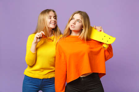Two pensive young blonde twins sisters girls in vivid clothes, heart eyeglasses hold yellow skateboard isolated on pastel violet blue background. People family lifestyle concept. Mock up copy space Stock Photo