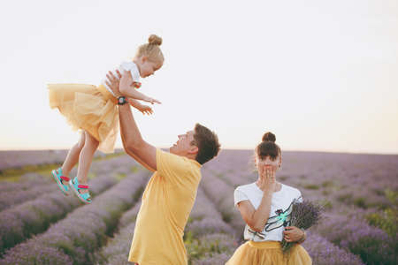 Young family in yellow clothes walk on purple lavender flower meadow field background, have fun, play with little cute child baby girl. Mother father, small kid daughter. Outdoors summer day concept 版權商用圖片