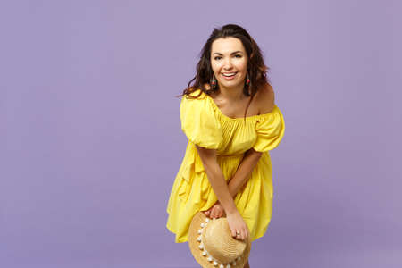 Portrait of smiling happy young woman in yellow dress holding summer hat looking camera isolated on pastel violet background in studio. People sincere emotions lifestyle concept. Mock up copy space