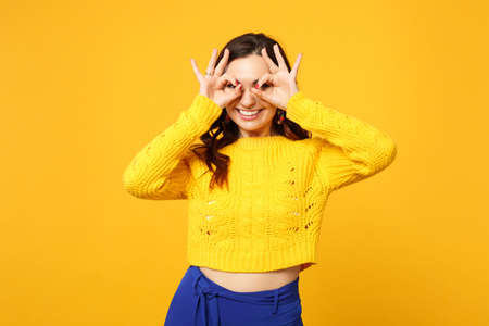 Smiling young woman in sweater, blue trousers hold hands near eyes imitating glasses or binoculars isolated on yellow orange background. People sincere emotions, lifestyle concept. Mock up copy space Stock Photo
