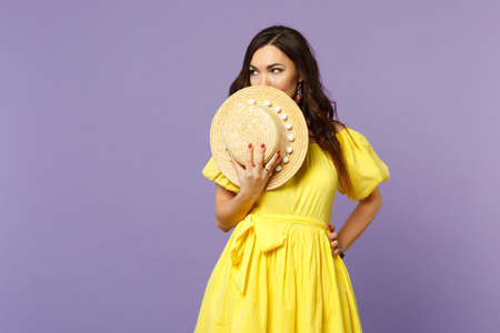 Portrait of attractive young woman in yellow dress covering face with summer hat looking aside isolated on pastel violet wall background. People sincere emotions lifestyle concept. Mock up copy space Banque d'images