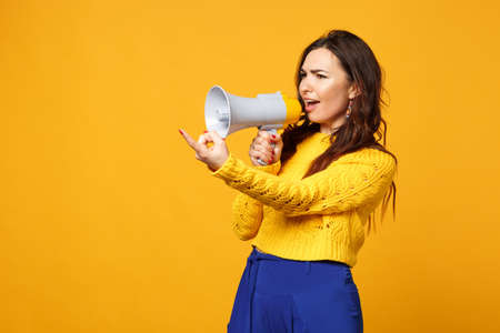 Perplexed young woman in sweater, blue trousers pointing index finger aside, scream in megaphone isolated on yellow orange background. People sincere emotions, lifestyle concept. Mock up copy space