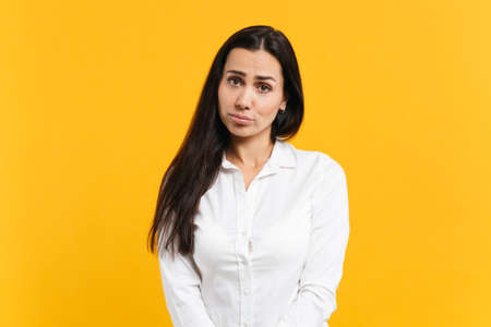 Portrait of upset offended young woman in white casual shirt standing and looking camera isolated on bright yellow orange wall background in studio. People lifestyle concept. Mock up copy space