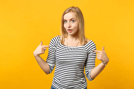 Portrait of amazed young woman in striped clothes pointing index fingers on herself isolated on yellow orange wall background in studio. People sincere emotions, lifestyle concept. Mock up copy space