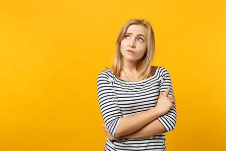Portrait of pensive young woman in striped clothes looking aside up holding hands crossed isolated on yellow orange background in studio. People sincere emotions lifestyle concept. Mock up copy space