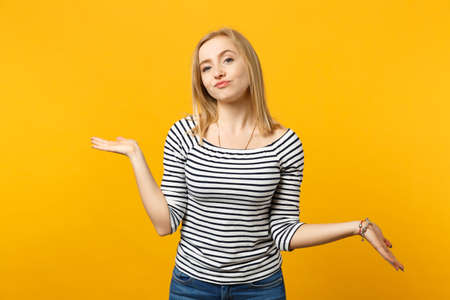 Arrogant haughty young woman in striped clothes spreading, pointing hands aside isolated on yellow orange wall background in studio. People sincere emotions, lifestyle concept. Mock up copy space