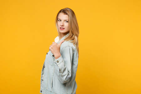 Side view of attractive young woman in denim casual clothes pointing thumb aside behind her back isolated on yellow orange wall background in studio. People lifestyle concept. Mock up copy space