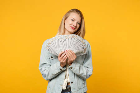 Portrait of pretty young woman in denim casual clothes hold fan of cash money in dollar banknotes isolated on yellow orange wall background in studio. People lifestyle concept. Mock up copy space
