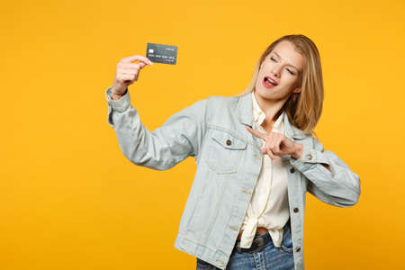 Portrait of cheerful young woman in denim casual clothes pointing index finger on credit bank card isolated on yellow orange wall background in studio. People lifestyle concept. Mock up copy space