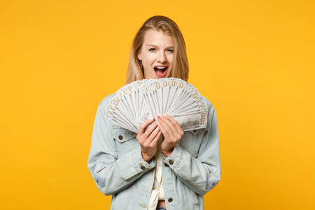 Portrait of excited young woman in denim casual clothes hold fan of cash money in dollar banknotes isolated on yellow orange wall background in studio. People lifestyle concept. Mock up copy space Reklamní fotografie
