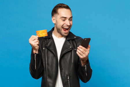 Handsome fun stylish young unshaven man in black jacket white t-shirt hold in hand cellphone, credit card isolated on blue background studio portrait. People lifestyle concept. Mock up copy space