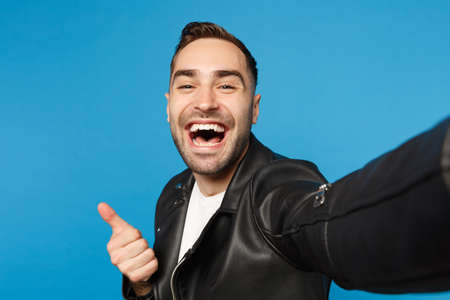 Close up selfie of stylish young unshaven man in black leather jacket white t-shirt looking camera isolated on blue background studio portrait. People sincere emotions concept. Mock up copy space
