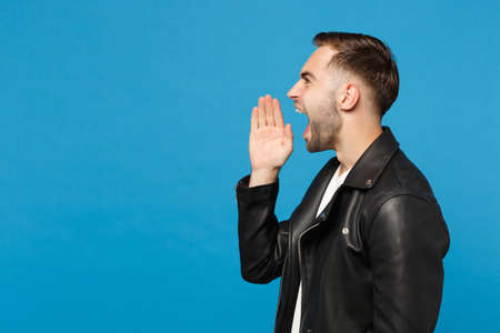 Young sad frustrated worried unshaven man in black jacket white t-shirt looking camera isolated on blue wall background studio portrait. People sincere emotions lifestyle concept. Mock up copy space Stock Photo