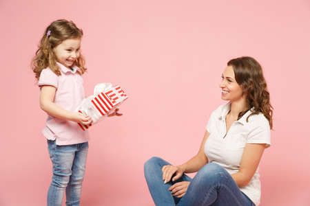 Woman have fun with cute child baby girl, hold present box. Mother little kid daughter isolated on pastel pink wall background, studio portrait. Mothers Day, love family parenthood childhood concept Stock Photo