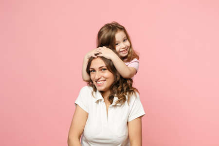 Woman in light clothes have fun with cute child baby girl. Mother, little kid daughter isolated on pastel pink wall background, studio portrait. Mothers Day love family, parenthood childhood concept