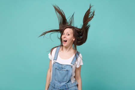 Excited young brunette woman girl in casual denim clothes posing isolated on blue turquoise wall background. People lifestyle concept. Mock up copy space. Fooling around jumping with flutterting hair.