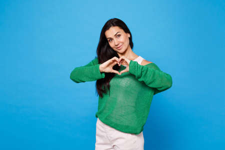 Portrait of charming pretty young woman in green casual clothes showing shape heart with hands, heart-shape sign isolated on bright blue wall background. People lifestyle concept. Mock up copy space.
