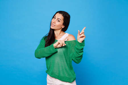 Portrait of amazed young woman in green casual clothes looking camera and pointing index fingers aside isolated on bright blue wall background in studio. People lifestyle concept. Mock up copy space.