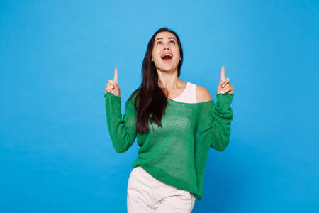 Portrait of excited young woman in green casual clothes keeping mouth open, pointing index fingers up isolated on bright blue wall background in studio. People lifestyle concept. Mock up copy space.