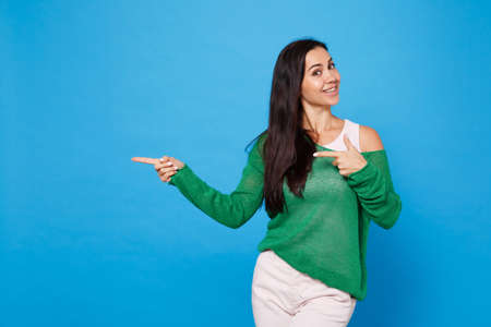 Portrait of smiling young woman in green casual clothes looking camera, pointing index fingers aside isolated on bright blue wall background in studio. People lifestyle concept. Mock up copy space.