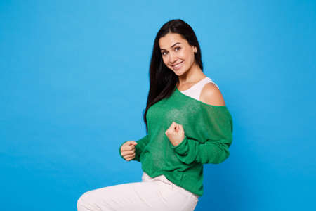 Portrait of smiling beautiful young woman in green casual clothes looking camera, doing winner gesture isolated on bright blue wall background in studio. People lifestyle concept. Mock up copy space.