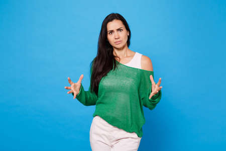 Portrait of displeased perplexed young woman in green casual clothes looking camera, spreading hands and fingers isolated on bright blue wall background. People lifestyle concept. Mock up copy space.