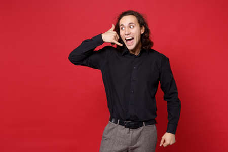 Young curly long haired man in black shirt posing isolated on red wall background studio portrait. People emotions lifestyle concept. Mock up copy space. doing phone gesture like says call me back.