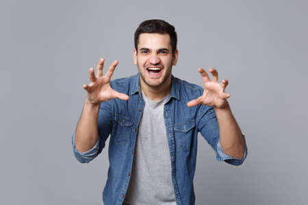 Handsome stylish unshaven young man in denim jeans shirt posing isolated on grey wall background studio portrait. People sincere emotions lifestyle concept. Mock up copy space. Sceptic shocked guy.