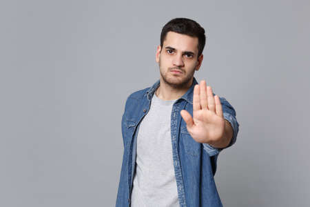 Angry mad sad upset unshaven young man in denim jeans shirt posing isolated on grey wall background studio portrait. People sincere emotions lifestyle concept. Mock up copy space. Stop palm gesturing.