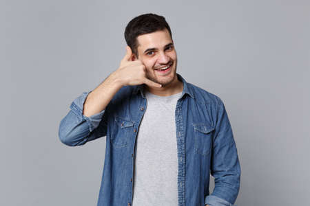 Handsome stylish unshaven young man in denim jeans shirt posing isolated on grey background studio portrait. People lifestyle concept. Mock up copy space. doing phone gesture like says call me back.