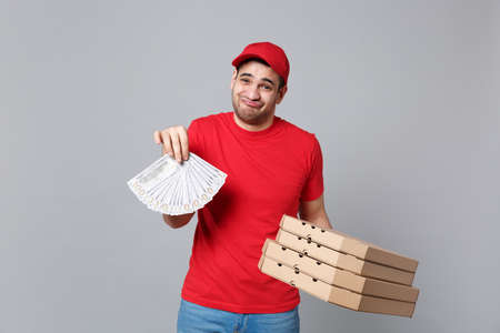 Delivery man giving hold cash money pizza boxes isolated on grey background. Professional male pizzaman employee in red cap t-shirt print working as courier dealer. Service concept. Mock up copy space